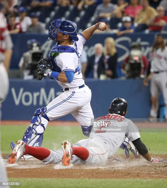 Xander Bogaerts of the Boston Red Sox slides across home plate to score a run in the eleventh inning during MLB game action as Luke Maile of the...
