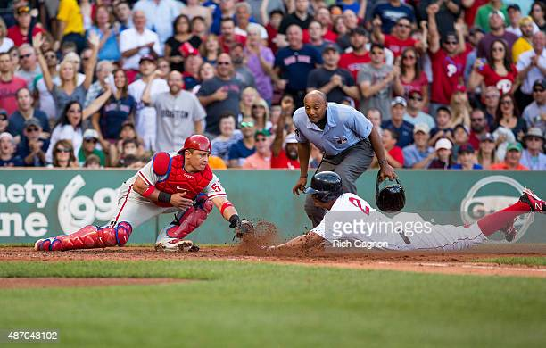 Xander Bogaerts of the Boston Red Sox slides home safely by Carlos Ruiz of the Philadelphia Phillies as he scores on an error after he hit a double...