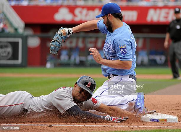 Xander Bogaerts of the Boston Red Sox slides into first as he tries to beat the throw to Eric Hosmer of the Kansas City Royals in the fifth inning...