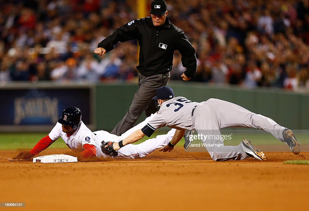 Xander Bogaerts #72 of the Boston Red Sox slides safely into second base following an attempted steal past Brendan Ryan #35 of the New York Yankees during the game on September 15, 2013 at Fenway Park in Boston, Massachusetts.