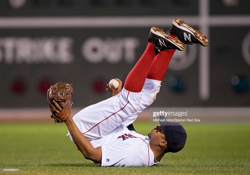 Xander Bogaerts #2 of the Boston Red Sox topples over after fielding a ground ball against the Colorado Rockies in the fifth inning on May 26, 2016 at Fenway Park in Boston, Massachusetts.