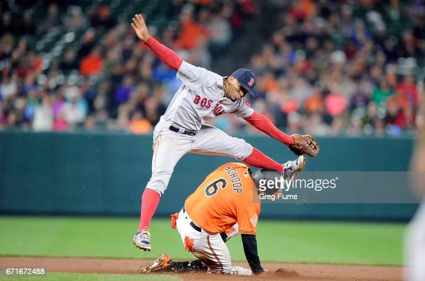 Xander Bogaerts of the Boston Red Sox tries to jump over Jonathan Schoop of the Baltimore Orioles after completing a double play in the eighth inning...
