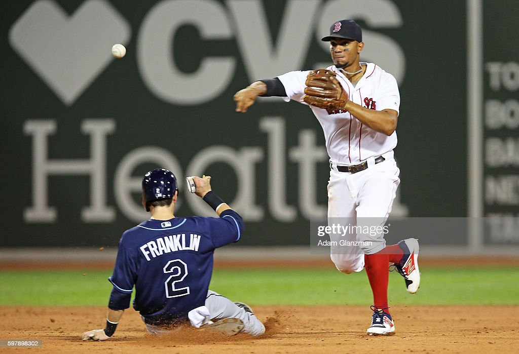Xander Bogaerts of the Boston Red Sox turns a double play over Nick Franklin of the Tampa Bay Rays in the ninth inning at Fenway Park on August 29...