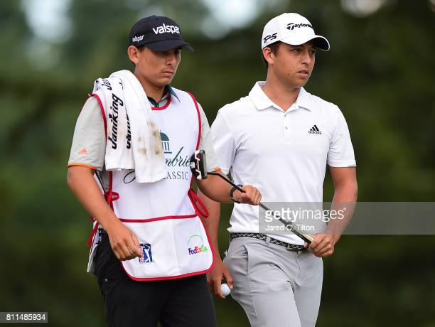 Xander Schauffele and his caddie reacts walks off the 16th green after a birdie putt during the final round of The Greenbrier Classic held at the Old...