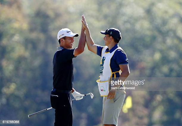 Xander Schauffele celebrates with his caddie after holing in on the second hole during the Final Round of the Sanderson Farms Championship at the...