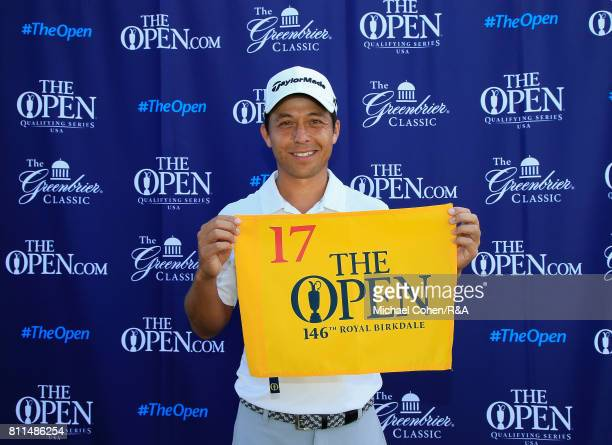Xander Schauffele holds a hole flag for qualifying for the Open Championship afterthe fourth and final round of The Greenbrier Classic held at The...