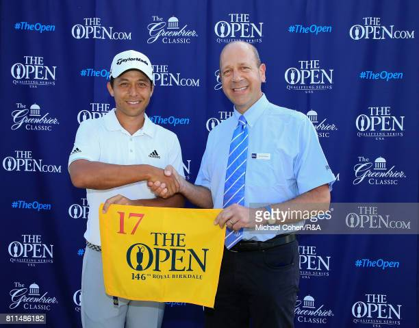Xander Schauffele is presented with a player badge and a hole flag by Charlie Maran of the R A Championship Committee after qualifying for the Open...