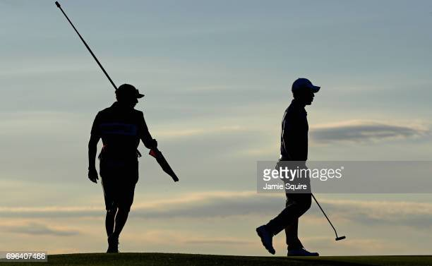 Xander Schauffele of the United States and caddie Austin Kaiser stand on the eighth green during the first round of the 2017 US Open at Erin Hills on...
