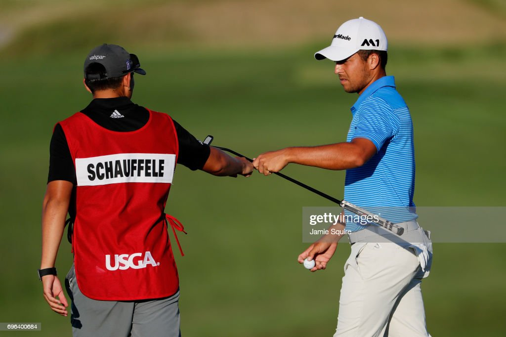 Xander Schauffele of the United States hands his club to caddie Austin Kaiser on the seventh hole during the first round of the 2017 U.S. Open at Erin Hills on June 15, 2017 in Hartford, Wisconsin.