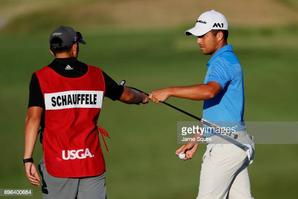 Xander Schauffele of the United States hands his club to caddie Austin Kaiser on the seventh hole during the first round of the 2017 US Open at Erin...