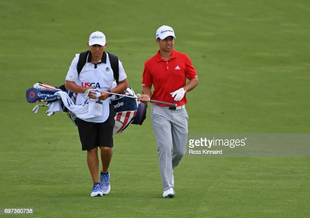 Xander Schauffele of the United States hands his club to caddie Austin Kaiser walks across the fourth hole during the final round of the 2017 US Open...