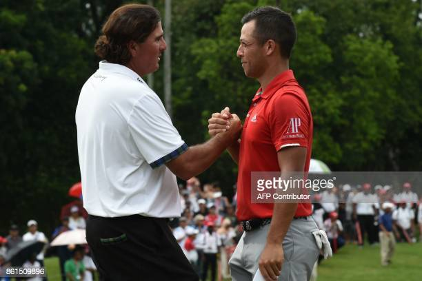 Xander Schauffele of the US congratulates Pat Perez of the US on the last hole after the final round of the 2017 CIMB Classic golf tournament in...