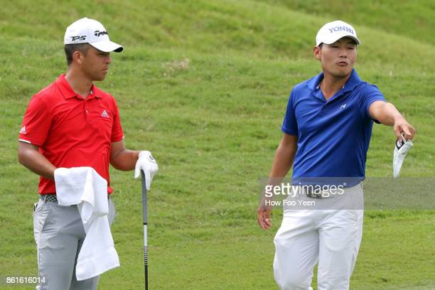 Xander Schauffele of USA chats with Sung Kang of Korea during the 2017 CIMB Classic at TPC Kuala Lumpur on October 15 2017 in Kuala Lumpur Malaysia