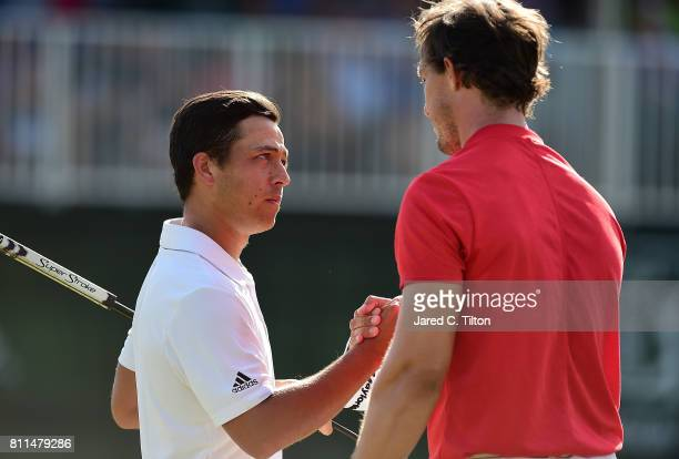 Xander Schauffele shakes hands with Jamie Lovemark after his birdie putt on the 18th green to take the outright lead during the final round of The...