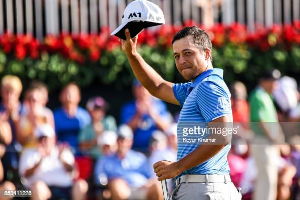 Xander Schauffele smiles and tips his cap to fans after his one stroke victory on the 18th hole green during the final round of the TOUR Championship...