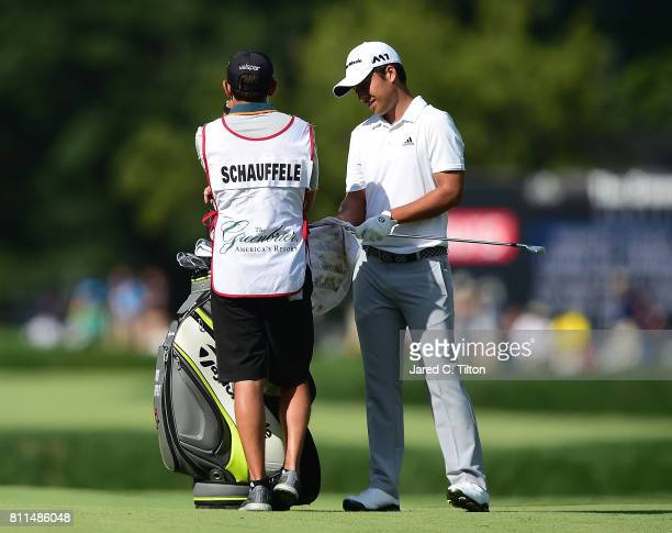 Xander Schauffele talks to his caddie before his second shot on the 17th hole during the final round of The Greenbrier Classic held at the Old White...