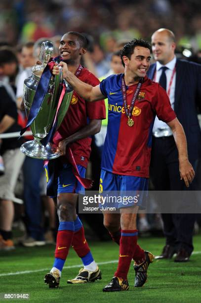 Xavi and Samuel Eto'o of Barcelona lift the trophy as they celebrate winning the UEFA Champions League Final match between Barcelona and Manchester...