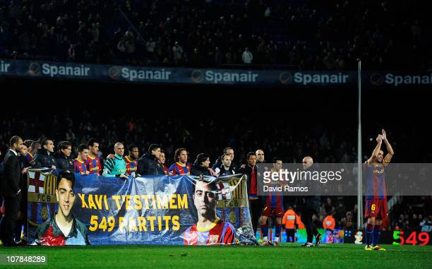 Xavi Hernandez of Barcelona acknowledges the crowd as his team mates hold a banner which reads 'Xavi we love you 549 games' at the end of the La Liga...