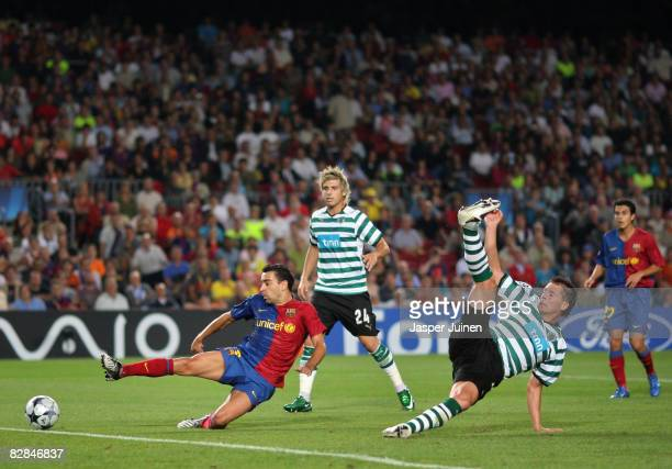 Xavi Hernandez of Barcelona scores his team's third goal past Anderson Polga and Miguel Veloso of Sporting Lisbon during the UEFA Champions League...