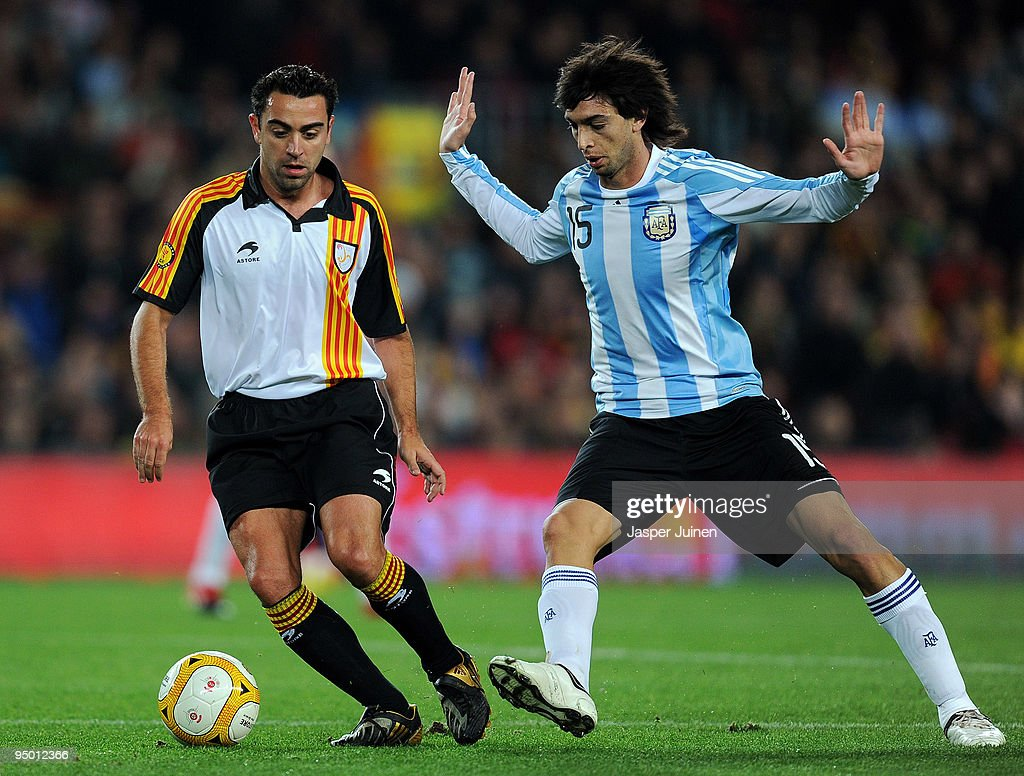 Xavi Hernandez (L) of Catalunya duels for the ball with <a gi-track='captionPersonalityLinkClicked' href=/galleries/search?phrase=Javier+Pastore&family=editorial&specificpeople=5857872 ng-click='$event.stopPropagation()'>Javier Pastore</a> of Argentina during the international friendly match between Catalunya and Argentina at the Camp Nou stadium on December 22, 2009 in Barcelona, Spain. Catalunya won the match 4-2.