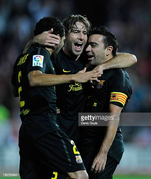 Xavi Hernandez of FC Barcelona celebrates beside Maxwell after scoring his team's opening goal during the La Liga match between Granada CF and FC...