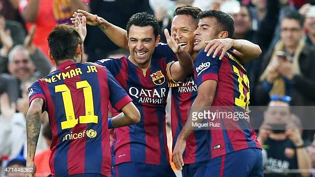 Xavi Hernandez of FC Barcelona celebrates with his teammates Neymar Adriano and Rafinha as he scored the fourth goal during the La Liga match between...