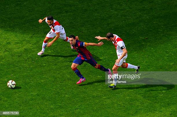 Xavi Hernandez of FC Barcelona competes for the ball with Javier Ignacio Aquino and Roberto Trashorras of Rayo Vallecano during the La Liga match...
