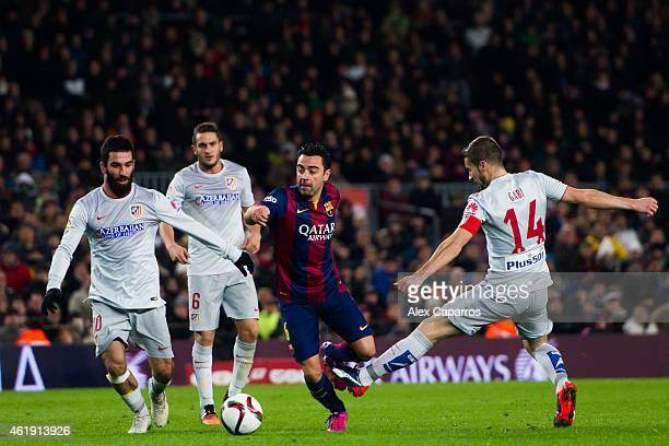 Xavi Hernandez of FC Barcelona conducts the ball between Arda Turan Jorge Resurreccion 'Koke' and Gabriel 'Gabi' Fernandez of Club Atletico de Madrid...