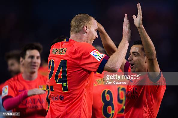 Xavi Hernandez of FC Barcelona congratulates his teammate Jeremy Mathieu after he scored the opening goal during the La Liga match between Celta Vigo...