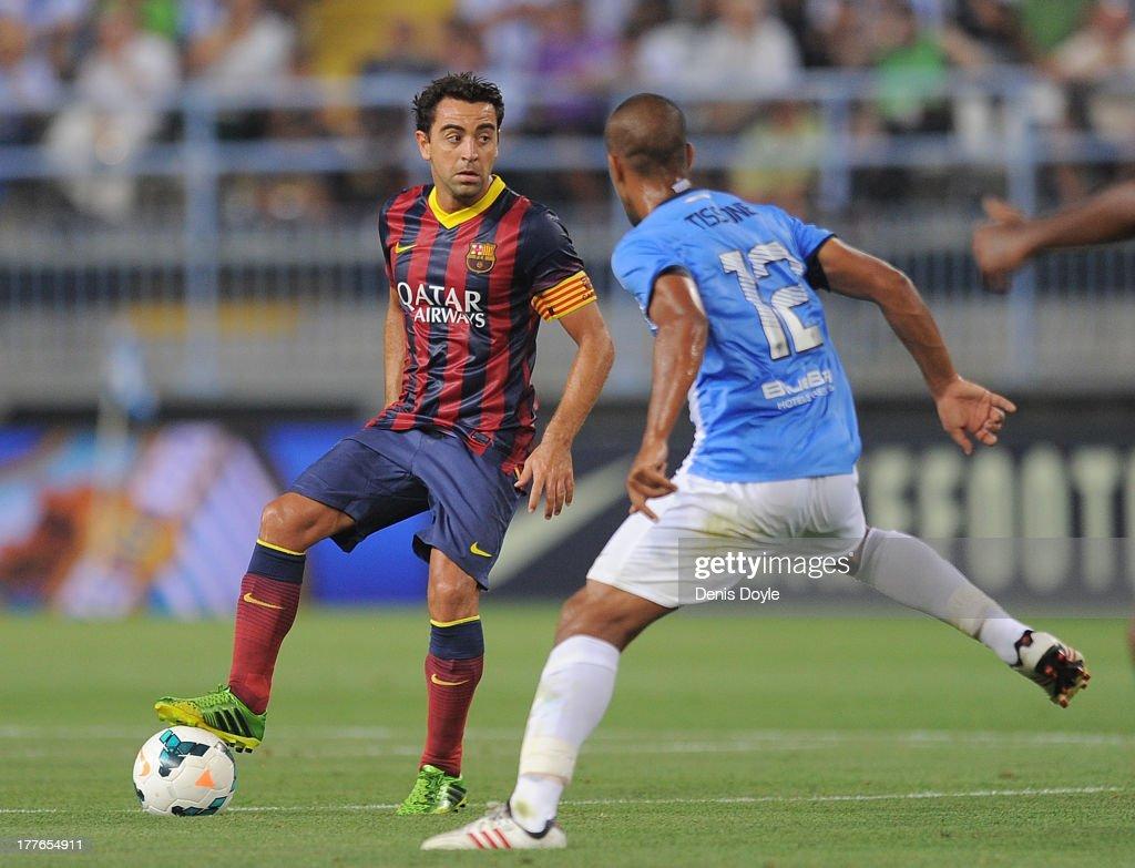 Xavi Hernandez (L) of FC Barcelona controls the ball beside Fernando Tissone of Malaga CF during the La Liga match between Malaga CF and FC Barcelona at La Rosaleda Stadium on August 25, 2013 in Malaga, Spain.