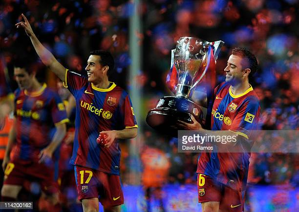 Xavi Hernandez of FC Barcelona holds the La Liga trophy alongside Pedro after the La Liga match between Barcelona and Deportivo La Coruna at Camp Nou...