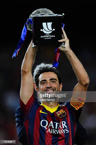 Xavi Hernandez of FC Barcelona holds up the trophy after winning the Spanish Super Cup during the Spanish Super Cup second leg match between FC...