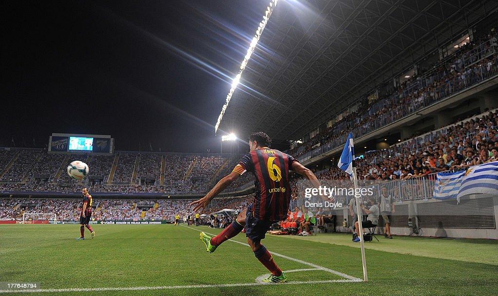 Xavi Hernandez of FC Barcelona takes a corner kick during the La Liga match between Malaga CF and FC Barcelona at La Rosaleda Stadium on August 25, 2013 in Malaga, Spain.