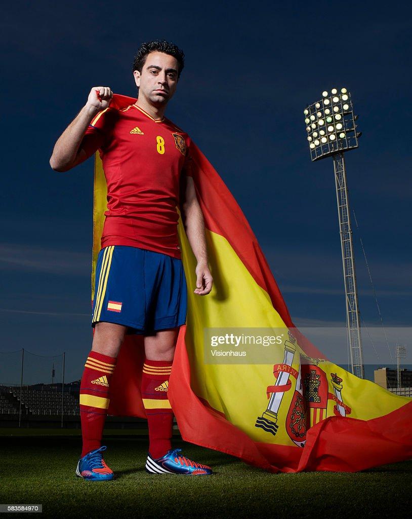 Xavi Hernandez of Spain holds the Spanish flag aloft