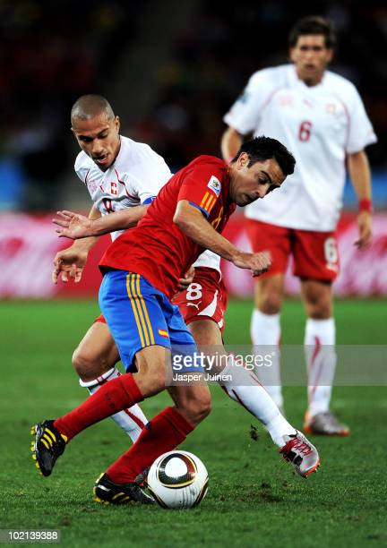 Xavi Hernandez of Spain is tackled by Gokhan Inler of Switzerland during the 2010 FIFA World Cup South Africa Group H match between Spain and...