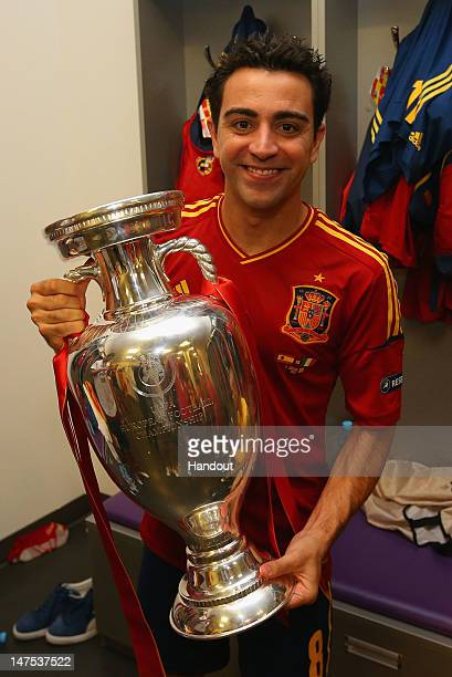 Xavi Hernandez of Spain poses with the trophy in the dressing room following the UEFA EURO 2012 final match between Spain and Italy at the Olympic...