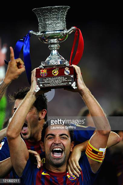 Xavi of Barcelona celebrates with the trophy after victory in the Super Cup second leg match between Barcelona and Real Madrid at Nou Camp on August...