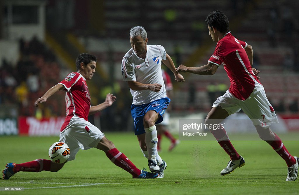 Xavier Baez of Toluca (L) fights for the ball with Pablo Alvarez of Nacional de Uruguay (R) during a match for the Bridgestone Libertadores Cup at Nemesio Diez on February 19, 2013 in Toluca, Mexico.