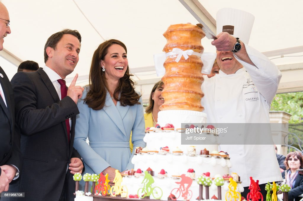 Xavier Bettel, Prime Minister of Luxembourg and Catherine, Duchess of Cambridge view a cake with a cycling design as they tour a cycling themed festival and unveil a mural of British cyclist Tom Simpson and Luxembourgish cycling legend Charly Gaul during a one day visit to Luxembourg at Place de Clairfontaine on May 11, 2017 in Luxembourg, Luxembourg.