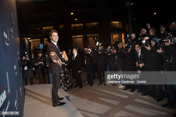 Xavier Dolan poses with his 2 awards as he arrives at the Cesar's Dinner at Le Fouquet's on February 24 2017 in Paris France