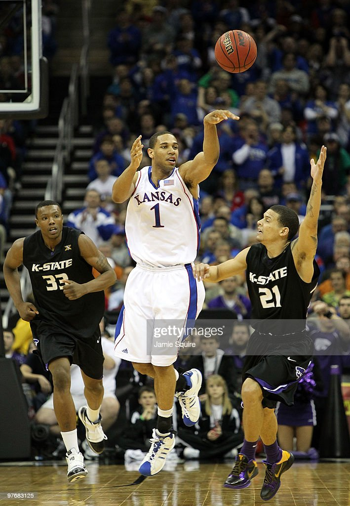 Xavier Henry of the Kansas Jayhawks passes as Wally Judge and Denis Clemente of the Kansas State Wildcats defend during the 2010 Phillips 66 Big 12...