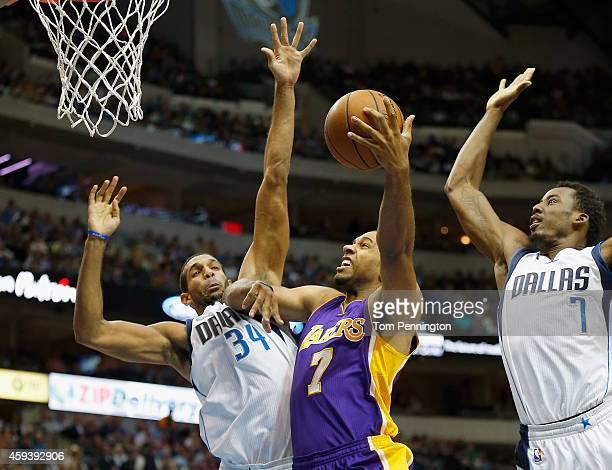 Xavier Henry of the Los Angeles Lakers drives to the basket against Brandan Wright of the Dallas Mavericks and AlFarouq Aminu of the Dallas Mavericks...