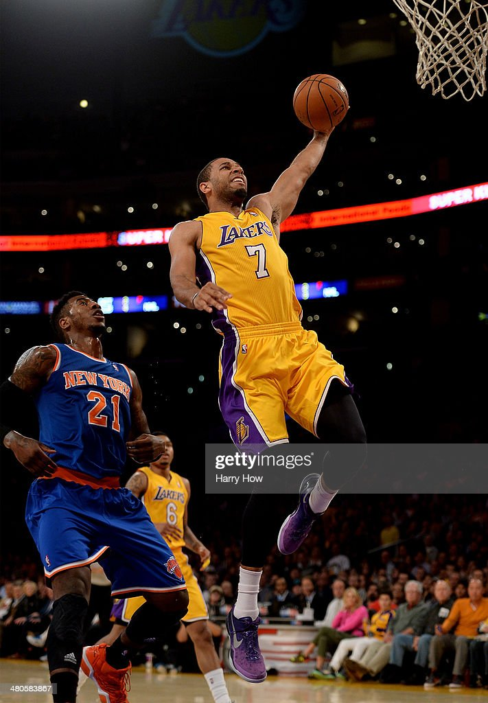 Xavier Henry of the Los Angeles Lakers dunks in front of Iman Shumpert of the New York Knicks at Staples Center on March 25 2014 in Los Angeles...