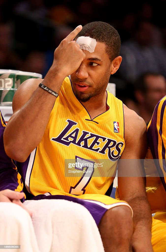 Xavier Henry #7 of the Los Angeles Lakers gestures to teammates on the bench after he receives a bandage for a cut on the forehead in the game with the San Antonio Spurs at Staples Center on November 1, 2013 in Los Angeles, California. The Spurs won 91-85.
