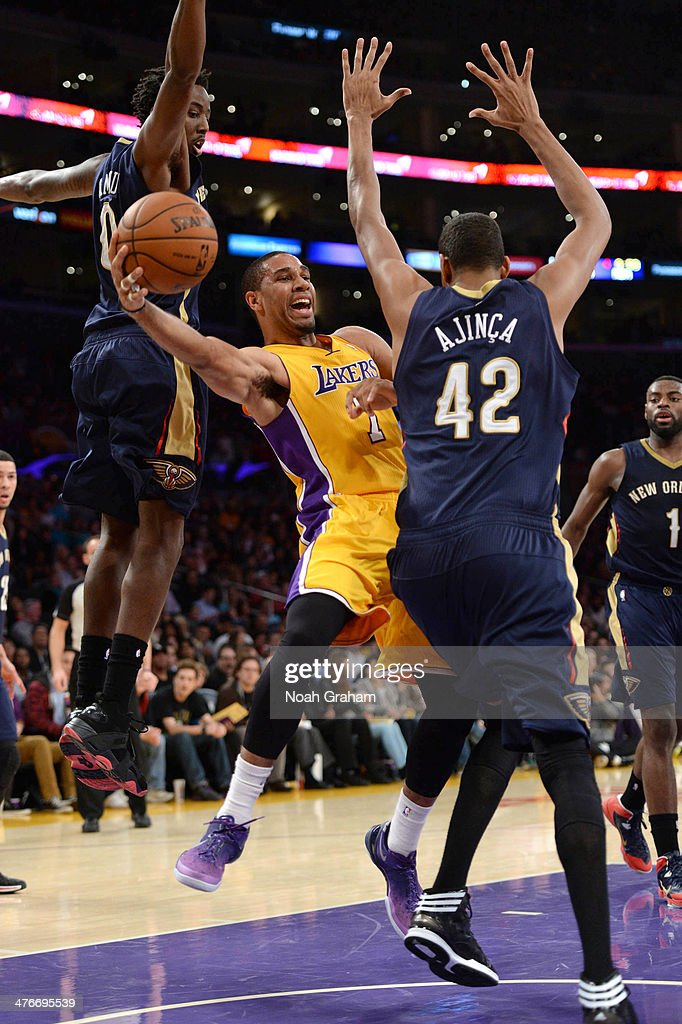 Xavier Henry #7 of the Los Angeles Lakers looks to pass against Alexis Ajinca #42 of the New Orleans Pelicans at Staples Center on March 4, 2014 in Los Angeles, California.