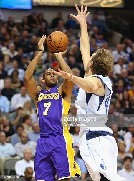 Xavier Henry of the Los Angeles Lakers takes a shot against Dirk Nowitzki of the Dallas Mavericks at American Airlines Center on November 5 2013 in...