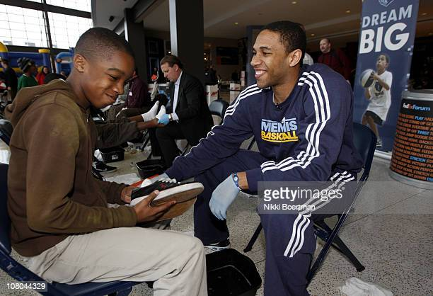 Xavier Henry of the Memphis Grizzlies helps with new shoes as he washes feet during a Samaritan's feet event on January 14 2011 at FedExForum in...