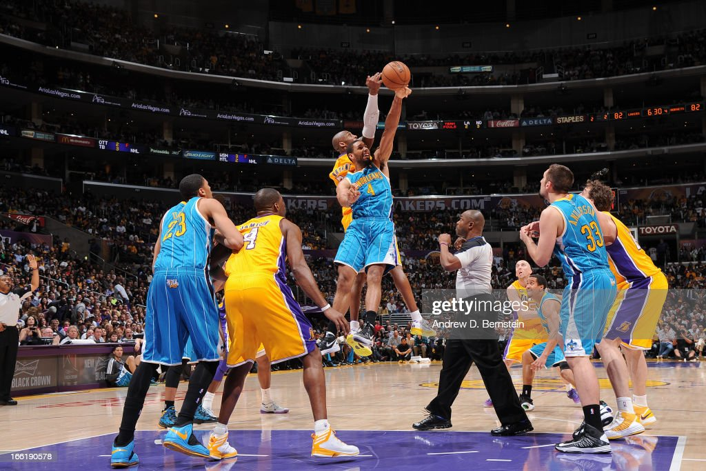 Xavier Henry #4 of the New Orleans Hornets and Kobe Bryant #24 of the Los Angeles Lakers reach for a jump ball at Staples Center on April 9, 2013 in Los Angeles, California.