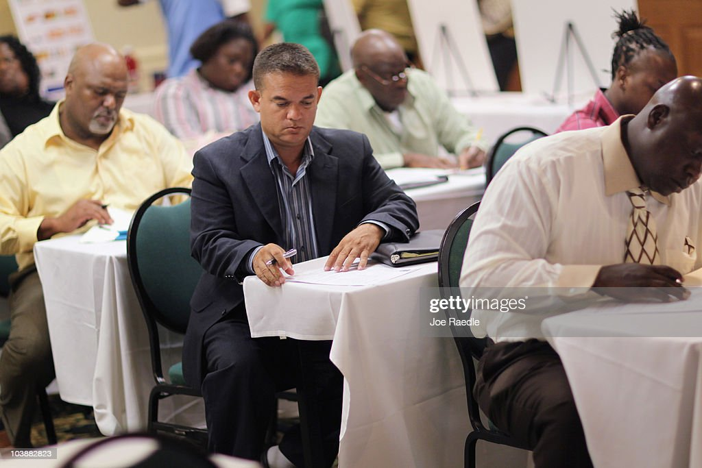 Xavier Lockart (C) fills out fills out a job application for grocery retailer ALDI as the company looks to fill job openings in one of the new stores opening in the South Florida area on September 7, 2010 in Fort Lauderdale, Florida. The unemployment rate in Florida has stayed around 11.5 percent.