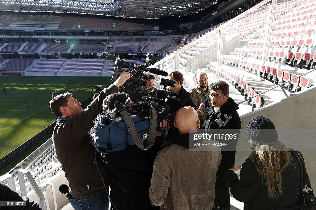 Xavier Lortat-Jacob, president of the Nice Eco-Stadium, (R) speaks to journalists on the tribune's balcony after an investigation has been launched into the violence that surrounded Sunday's French Ligue 1 match between Nice and Saint-Etienne, on November 25, 2013 at the Allianz Riviera stadium in Nice, southeastern France. Eight people were hurt after fans from the two sides tore up seats inside the Allianz Riviera stadium in Nice and hurled them at each other. AFP PHOTO / VALERY HACHE